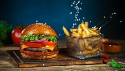 French fries fall next to cheeseburger, lying on vintage wooden cutting board, Freeze motion.