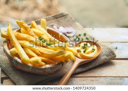 French fries in a basket placed on a wooden background