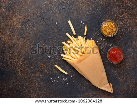 French fries in a paper bag with sauces. Top view #1062384128