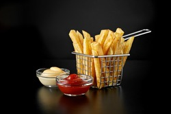 French fries in basket with ketchup and sauce isolated on black background. Front view.