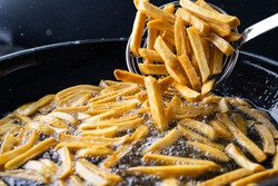 French fries in the deep fryer are fried in hot fat