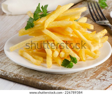 Shutterstock French fries on  wooden board. Selective focus