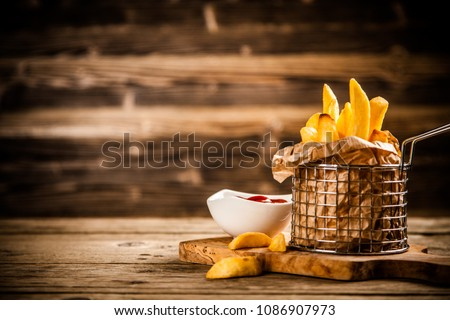 French fries on wooden table #1086907973