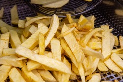 French fries potatoes frying in boiling oil. Fat and tasty food. Fast food. Cooking french fries  in Irish  shop Dublin
