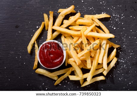 French fries with ketchup on dark background, top view #739850323