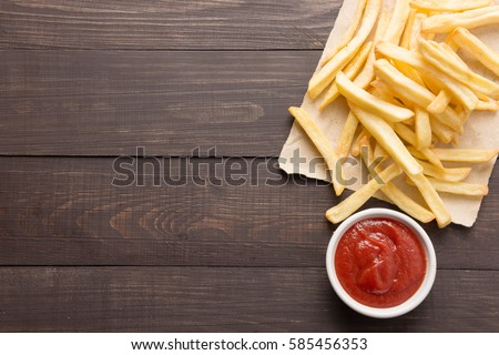 French fries with ketchup on wooden background. #585456353