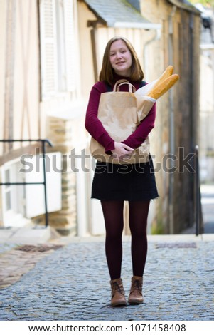 French girl with baguettes on the street side of the city
