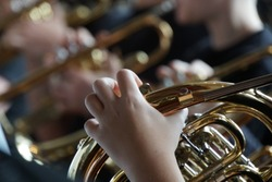 French horn and child hands. Musical brass instruments, adults and children. Concert in the school.