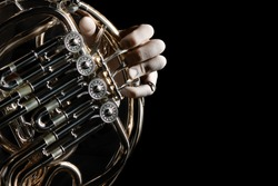 French horn instrument. Hands playing horn player close up isolated on black