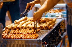 French hotdog stand at a market place. a person is about to grap a sausage.