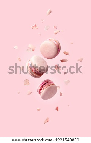 French macarons flying in the air among the crumbs on pink background. Levitation concept. food background. Pastel color.