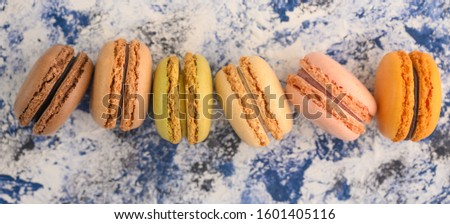 French macaroons in a row of colored, on a colored background with colored caramel sweets.