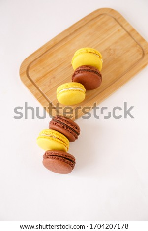 French macaroons on a wooden board.  Macaroons on a light background. Six macaroons on a wooden board.  Lemon and chocolate macaroons (yellow and brown).