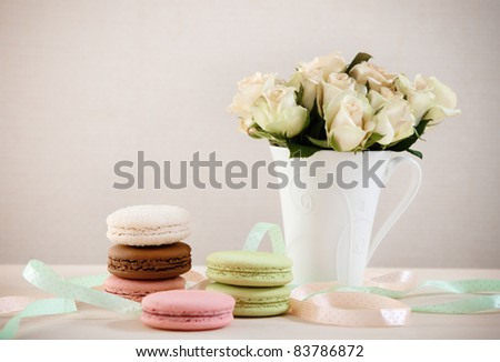 French macaroons on the table decorated with ribbons and roses