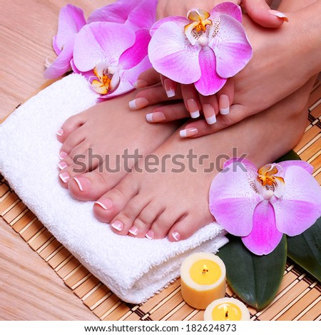 French Manicure on Beautiful Female Feet and Hands with pink orchid flowers on bamboo mat. Nail care. Pedicure. Spa Salon
