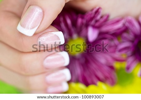 French manicure on the hands of  woman near the flowers