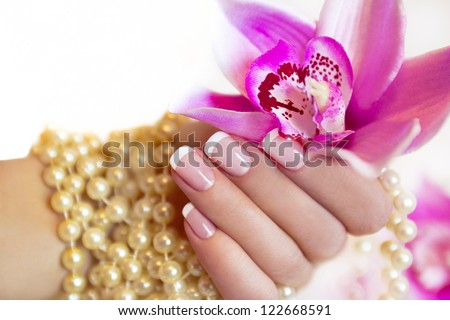 French Manicure To A Woman\'S Hand With An Orchid And Beads.