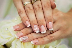 French manicure with white ornament, flowers and strasses, hands of the bride close-up on a bouquet of white roses.