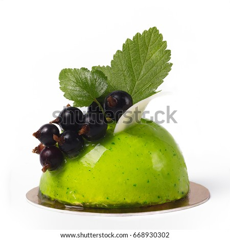 French mousse hemispherical cake covered with pistachios glaze. Green modern European dessert decorated of a branch black currant and fresh berries