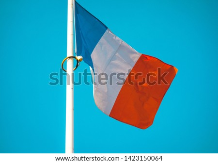 French national flag flying from a flagpole on a white flagpole in a close up view as it waves in the wind against a blue sky #1423150064