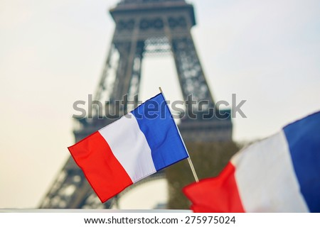Stock Photo French national flag (tricolour) in Paris with the Eiffel tower in the background