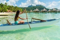 French Polynesia Tahiti travel vacation concept. Outrigger Canoe polynesian watersport sport woman paddling in traditional vaa boat. Water leisure activity, Bora Bora overwater bungalow resort hotel
