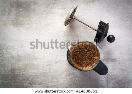 French press coffee maker on concrete table