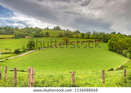 French Pyrenees Mountains rural view behind agricultural fencing, dramatic overcast sky, pilgrims in the distance, leaving Saint-Jean-Pied-de-Port, France