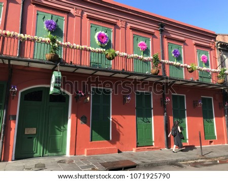 French Quarter architecture in New Orleans, Louisiana. House in French Quarter in 18th century Spanish style with cast iron galleries and pastel colors. House is deep orange color with green doors.