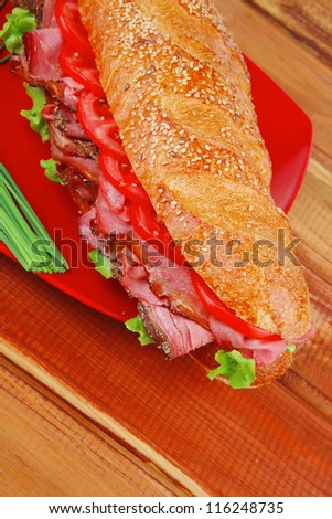 french sandwich : fresh white baguette with chicken smoked sausage on red ceramic plate over wooden table