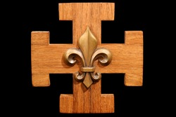 French Scout Emblem - Antique scouting fleur-de-lis on solid oak wood.  Isolated on black background.
