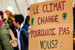 French sign at environmental protest. A French poster is viewed close-up, saying the climate is changing, why not you, as during an ecological activism march on a street in Montreal, Canada