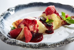French Style Crepes - Cream Crepes with Berry and Fruit. Pancake Breakfast on white and blue plate isolated on white background. Mixed berry crepes garnished with mint and sweet sauce. Closeup view