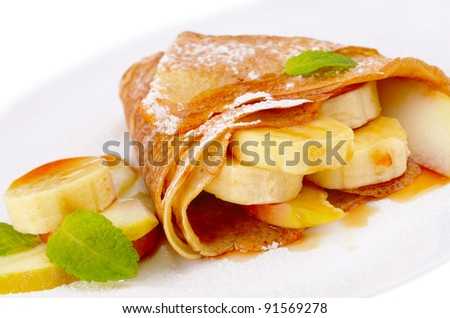 French style crepes with banana, maple syrup and sugar powder isolated on white