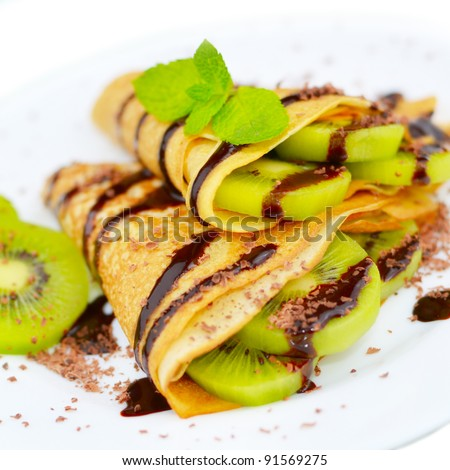 French style kiwi crepes with chocolate sauce and chips isolated on white