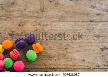 french sweet delicacy, colourful macaroons variety with wood Background,vintage tone - Shutterstock ID 409438087