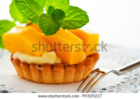 French tart with mango and vanilla pudding on white background as a studio shot