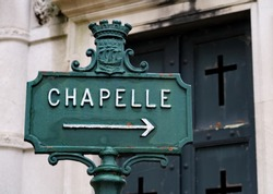 French text: Chapelle. English translation: Chapel. Inscription on an iron panel in a cemetery.