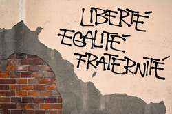 French text Liberte, Egalite, Fraternite ( Liberty, Equality, Fraternity ) - Handwritten graffiti on the wall, anarchist aesthetics. Revolutionist motto. Appeal to fight for republic and constitution
