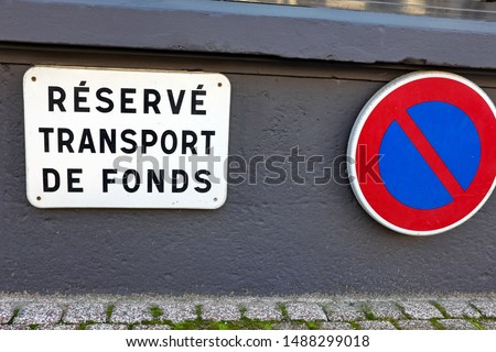 French text: Réservé aux transports de fonds.English translation:  For cash transportation only. Sign prohibiting parking on the street. #1488299018
