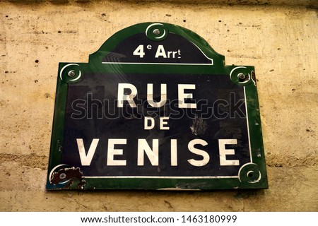 French text: Rue de Venise. English translation: Venice street. Street name sign on a stone facade. Paris, France.