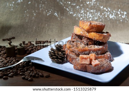 French toast, sliced sweet bread, unfocused foreground. Selective focus .Coffee beans. Rabanada brasileira .White dish, dark background .Christmas sky.Breakfast.View from above. rom above. #1513325879