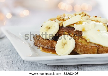 French toast topped with sliced bananas, nuts, cream cheese sauce and caramel syrup. Extreme shallow depth of field with selective focus on french toast and some blur on corner of plate.