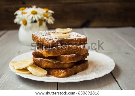 french toast with banana and daisies on wooden background