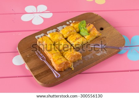 french toast with butter and milk on Wooden pink background #300556130