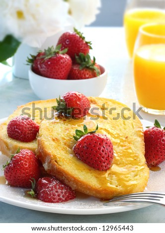 French toast with fresh strawberries, maple syrup and powdered sugar, and orange juice behind.  A sunny, healthy breakfast.