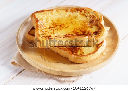 french toast with honey syrup on wooden plate