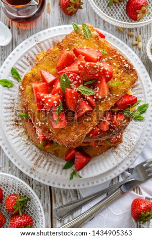 French toasts, French toasts made of sliced brioche with fresh strawberries, cinnamon, sesame seeds and honey on a plate, top view.  Delicious breakfast or dessert #1434905363