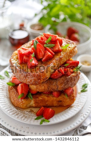 French toasts, French toasts made of sliced brioche with fresh strawberries, honey and mint. Delicious breakfast or dessert #1432846112