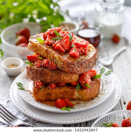 French toasts, French toasts made of sliced brioche with fresh strawberries, honey and mint, sprinkled sesame seeds. Delicious breakfast or dessert #1432943897